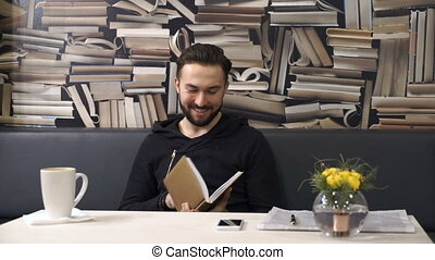 Businessman is cheking his planner sitting at the table