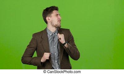 Businessman is dancing energetically, he is having fun. Green screen