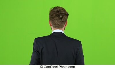 Businessman is going to a meeting and waving greetings. Green screen. Back view