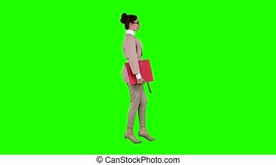 Businessman is going to a meeting with a red folder. Green screen. Side view. Slow motion