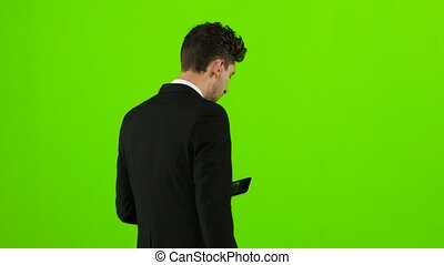Businessman is going to work and prints important messages. Green screen. Back view