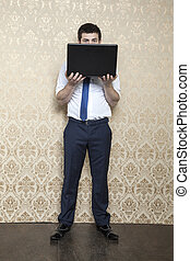 businessman is hiding behind a laptop