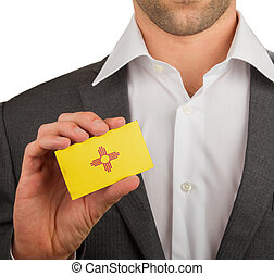 Businessman is holding a business card, flag of New Mexico