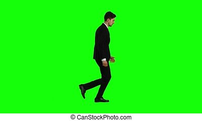 Businessman is in a hurry to work, he starts to run. Green...