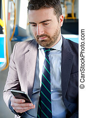 Businessman is looking at his mobile phone