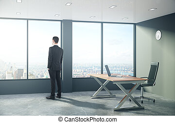 Businessman is looking out the window in modern loft style office