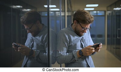Businessman is playing games on phone in office
