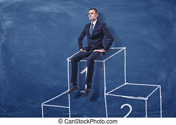 Businessman is sitting on the first place of a podium on blue blackboard background