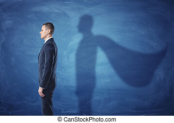 Businessman is standing in profile casting a shadow of the...
