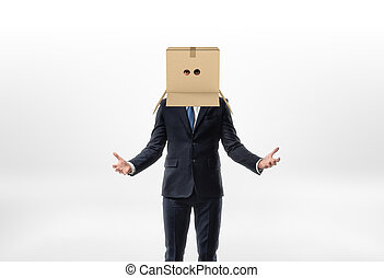 Businessman is staying his hands to the sides with a box on his head with holes for eyes on white background