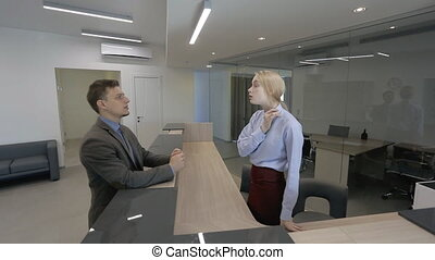 Businessman is talking to blond female secretary at the office reception.