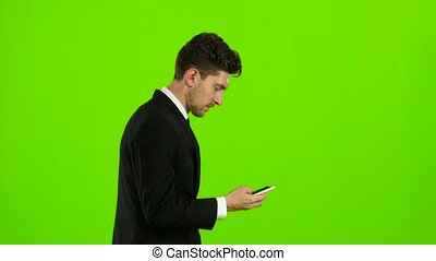 Businessman is walking on the road talking on the phone. Green screen. Side view