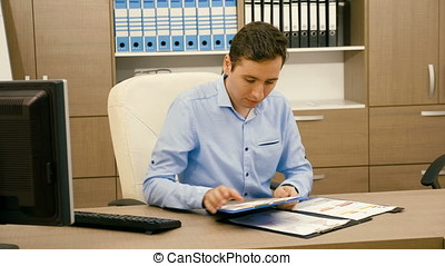 Businessman is working in his office and looking on charts in a folder