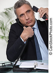 Businessman juggling two telephones