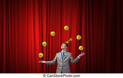 Businessman juggling with balls - Young businessman in cap...