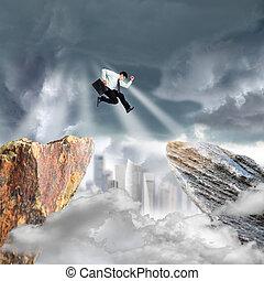Businessman jump over precipice mountain rock