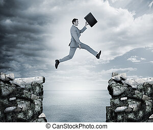 Businessman jumping a gap between cliffs with the sea on the...