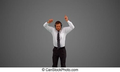 Businessman jumping and listening to music