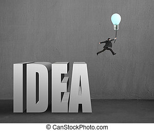 Businessman jumping from idea concrete word to catch glowing lamp balloon in concrete wall background