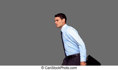 Businessman jumping on grey screen in slow motion