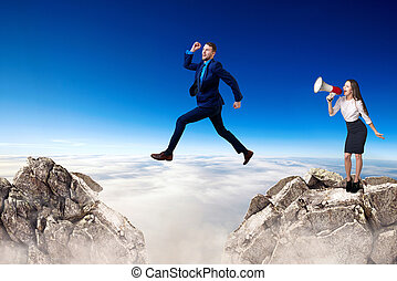 Businessman jumping over a cliff and boss is cheering with bullhorn.