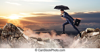 Businessman jumping over a cliff with umbrella and briefcase.