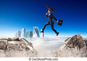 Businessman jumping over a cliff with umbrella over blue sky background.