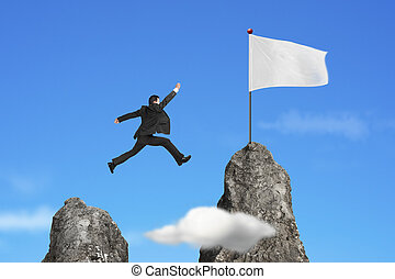 businessman jumping over mountain peak to blank flag with sky