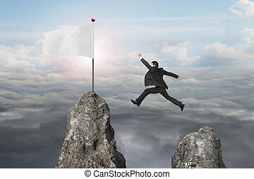 businessman jumping over mountain peak to blank flag with sunlig