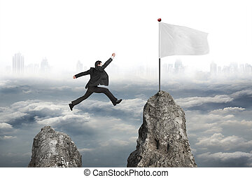 businessman jumping over mountain peak to flag with cloudy citys