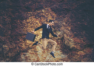 businessman jumping over the mountain