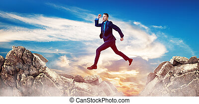 Businessman jumping through the gap among mountains.