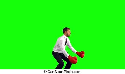 Businessman jumping with boxing gloves and punching on green...
