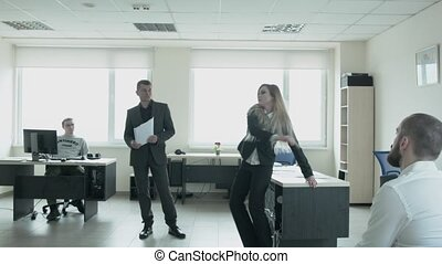 Businessman jumps in the office and dances in front of colleagues at work. The stern blonde performs a ritual dance for business.