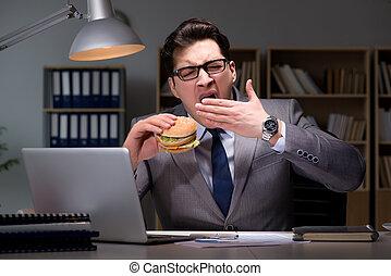 Businessman late at night eating a burger