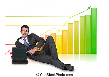 Businessman laying with laptop in front of bar chart