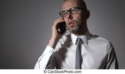 Businessman leads a serious conversation with a colleague on the phone.