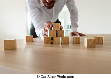 Businessman leaning in to carefully assemble pyramid shape with blank wooden blocks