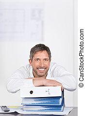 Businessman Leaning On Binders At Desk