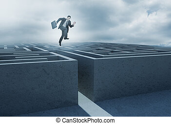 Businessman leaping above a maze