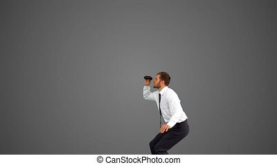 Businessman leaping and holding binoculars on grey...