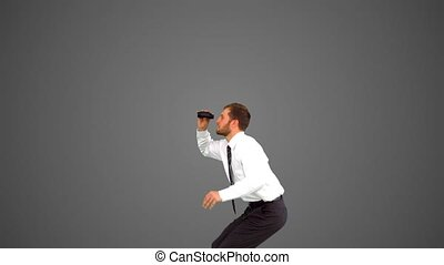 Businessman leaping and holding tablet on grey background in...