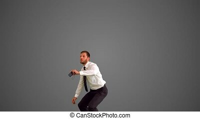 Businessman leaping and taking self portrait on grey...