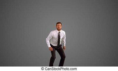 Businessman leaping on grey background in slow motion