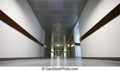 Businessman leaves through corridor in office, part1 -...