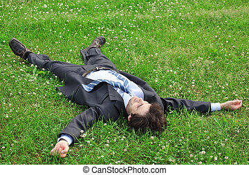 businessman lies on back on grass, having stretched legs and hands