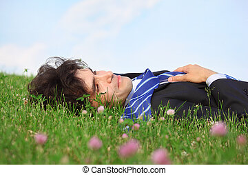 businessman lies on back on grass with closed eyes