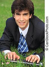 businessman lies on grass with laptop