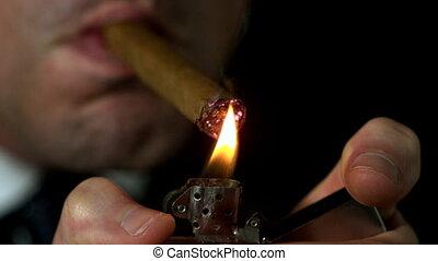 Businessman lighting his cigar on black background in slow...