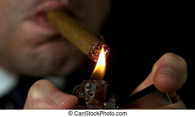 Businessman lighting his cigar on black background in slow motion